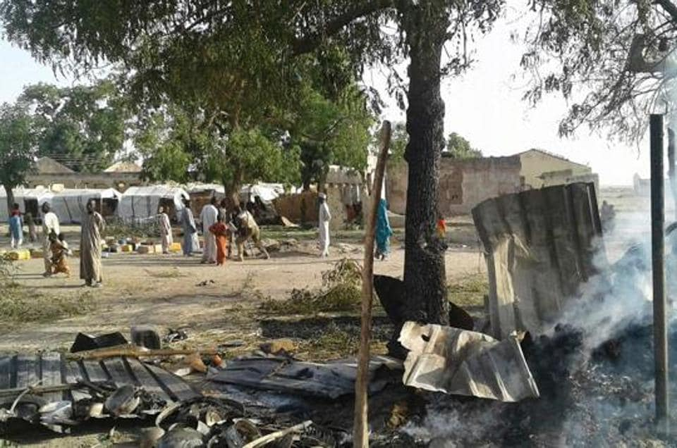 This handout image received courtesy of Doctors Without Border (MSF) on January 17, 2017, shows people standing next to destruction after an air force jet accidentally bombarded a camp for those displaced by Boko Haram Islamists, in Rann, northeast Nigeria.