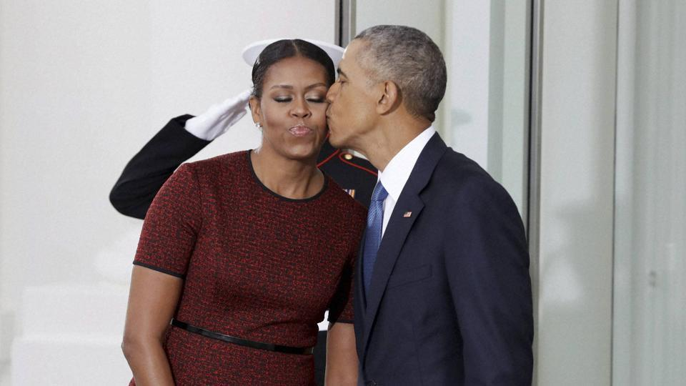 President Barack Obama kisses first lady Michelle Obama as they await for the arrival of President-elect Donald Trump and his wife Melania on Friday at the White House in Washington.