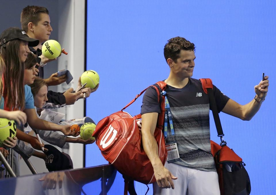 Milos Raonic takes a selfie for a fan after defeating France's Gilles Simon 6-2, 7-6 (7/5), 3-6, 6-3. (AP)