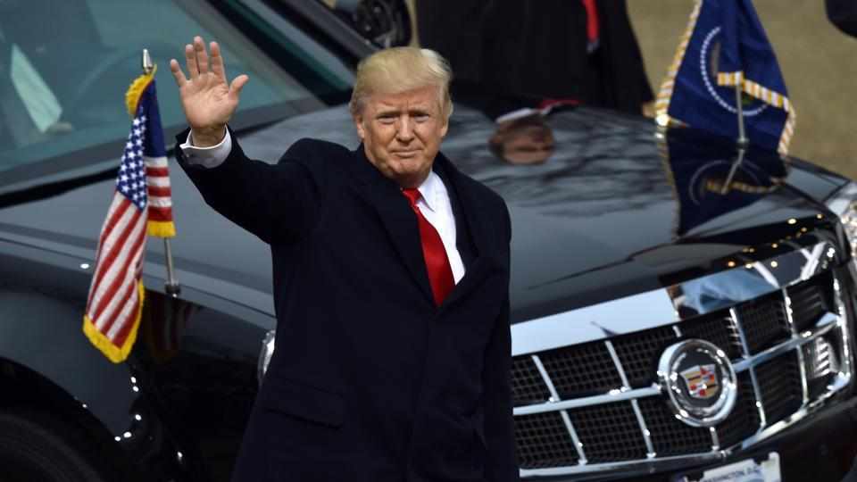 US President Donald Trump waves as he arrives in front of the White House for the presidential inaugural parade on January 20.