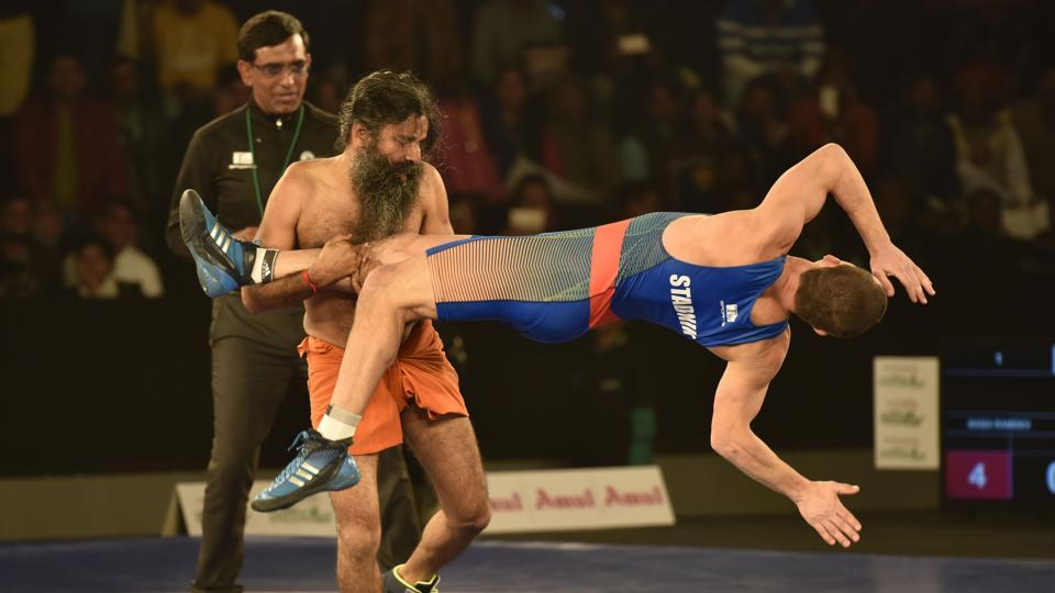Baba Ramdev and Andrey Stadnik, Olympic Medalist in action during the Pro Wresting league-2 at K D Jadhav Stadium, I G Stadium in New Delhi. (Virendra Singh Gosain/HT PHOTO)