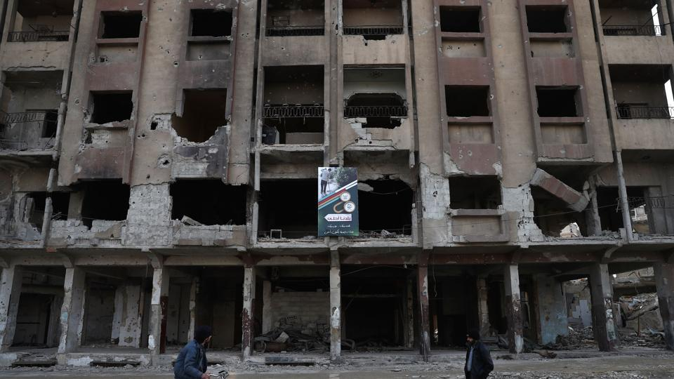 Syrians walk past a damaged building in the rebel-held town of Douma, on the eastern outskirts of the capital Damascus, on January 20.
