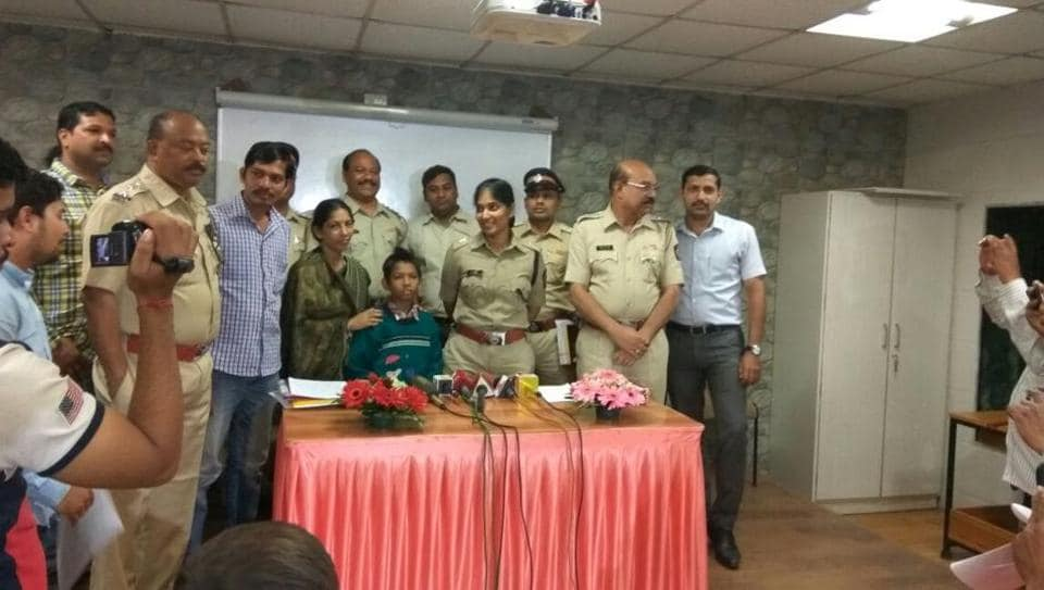 The rescued boy and his parents with the police team.