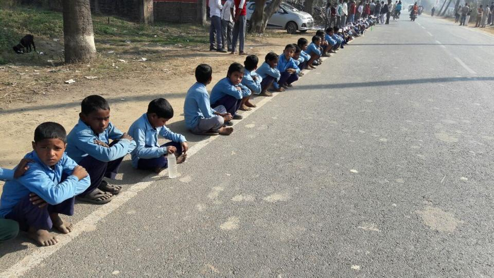 Schoolchildren sit on the flank of  a main road at Dhaka in Bihar's East Champaran district for the human chain programme.