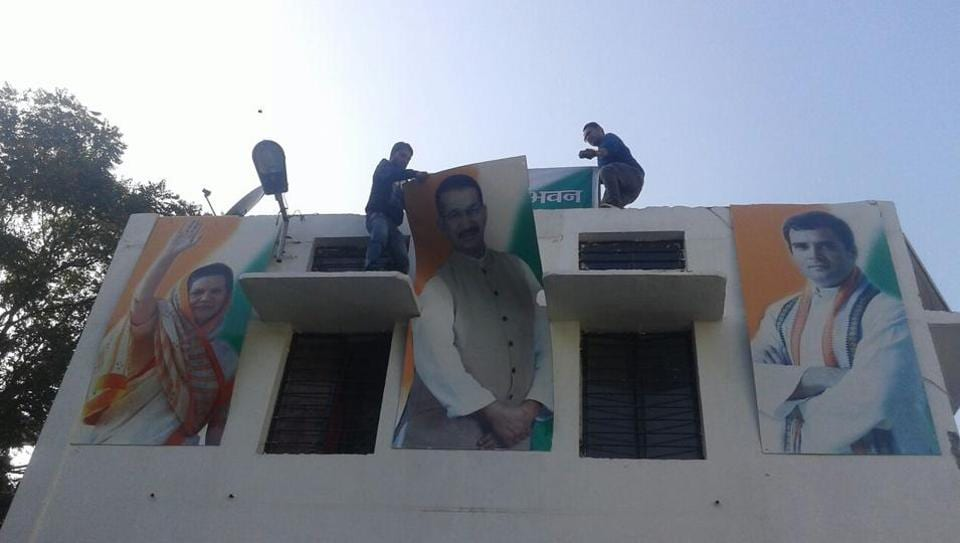 Congress workers take down posters of state party chief Kishore Upadhyay in Dehradun on Sunday after candidates list for the Uttarakhand assembly elections was announced.