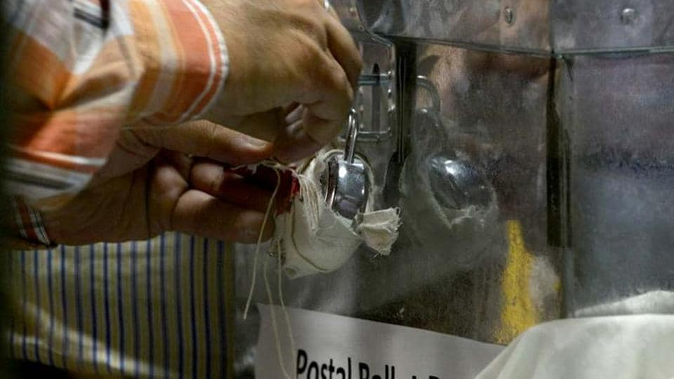 An Indian election commission officer opens a postal ballot box at a counting centre in New Delhi
