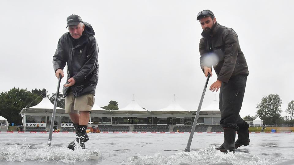 Groundstaff pushes water off the covers in Christchurch during the New Zealand-Bangladesh second Test's third day which was washed out.