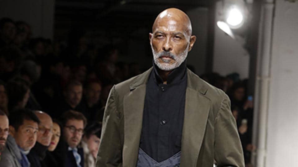A model presents a creation by Yohji Yamamoto. The house offered a quirky take on three-piece suits, featuring waistcoats with scooped out necklines and shirts that buttoned up to the jawline. (AFP)