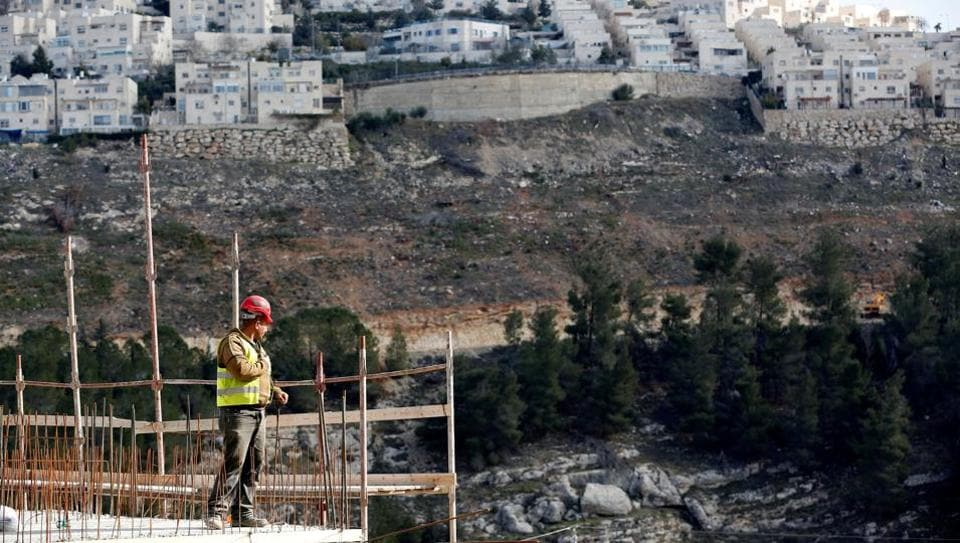 A labourer works at a construction site in the Israeli settlement of Ramot, as the Israeli settlement of Ramat Shlomo is seen in the background, in an area of the occupied West Bank that Israel annexed to Jerusalem January 22, 2017.