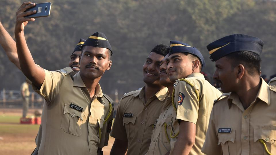Mumbai police personnel take a selfie during a parade rehearsal ahead of the Republic Day.
