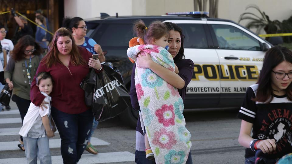 San Antonio police help shoppers exit the Rolling Oaks Mall, Sunday, Jan. 22, 2017, in San Antonio, after a deadly shooting. Authorities say several were injured after a robbery at the shopping mall.