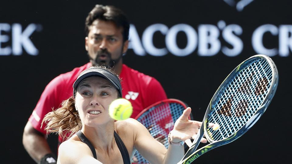 Switzerland's Martina Hingis hits a backhand as partner India's Leander Paes watches during their mixed doubles match against Nikola Mektic and Brian Baker. (AP)
