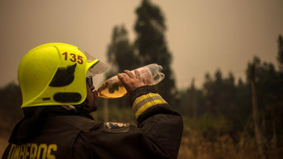 A fireman takes a break as others battle the worst forest fires for over 10 years in central Chile. (Martin Bernetti/AFP)
