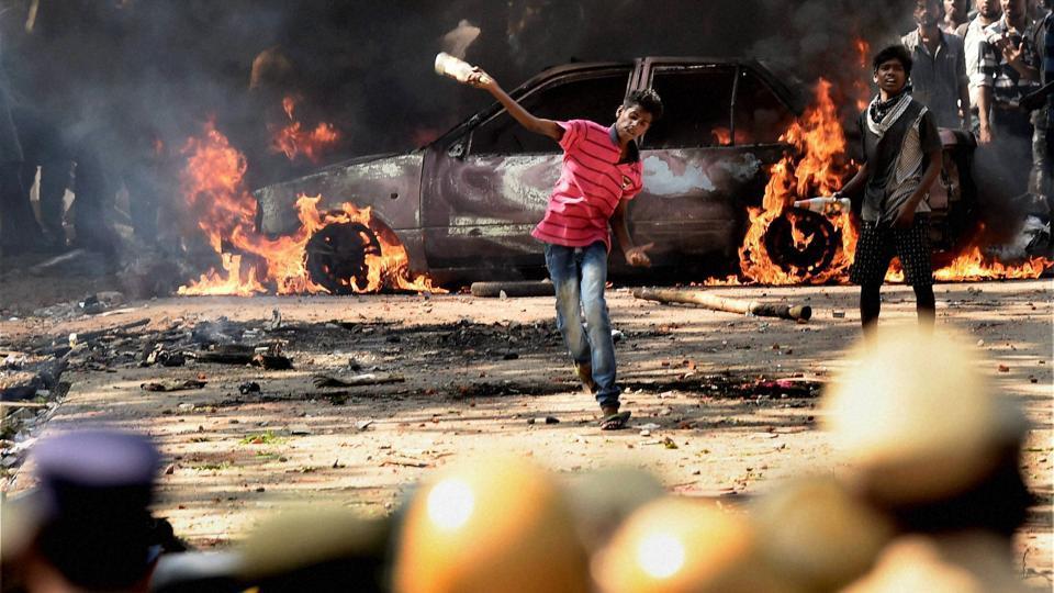 A pro-Jallikattu protester throws bottles at policemen during a clash near Marina Beach in Chennai.