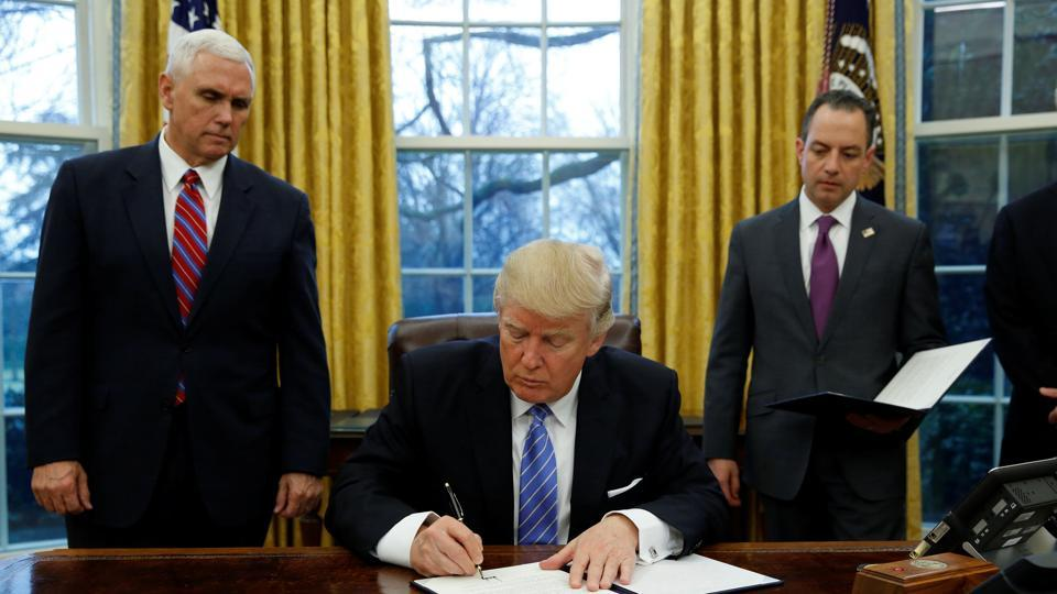 US President Donald Trump signs an executive order on US withdrawal from the Trans Pacific Partnership while flanked by Vice President Mike Pence (L) and White House Chief of Staff Reince Priebus (R) in the Oval Office of the White House in Washington.