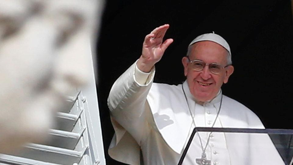 Pope Francis waves as he leads his Sunday Angelus prayer in Saint Peter's square at the Vatican on January 22, 2017.