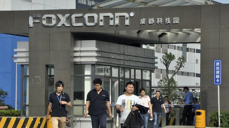 Workers walk out of the entrance to a Foxconn factory in Chengdu, Sichuan province. Apple and its suppliers such as Taiwanese tycoon Terry Gou's Foxconn Technology Group have been the target of labour rights groups, which say the world's most valuable technology company are making iPhones and iPads in massive sweat shops.
