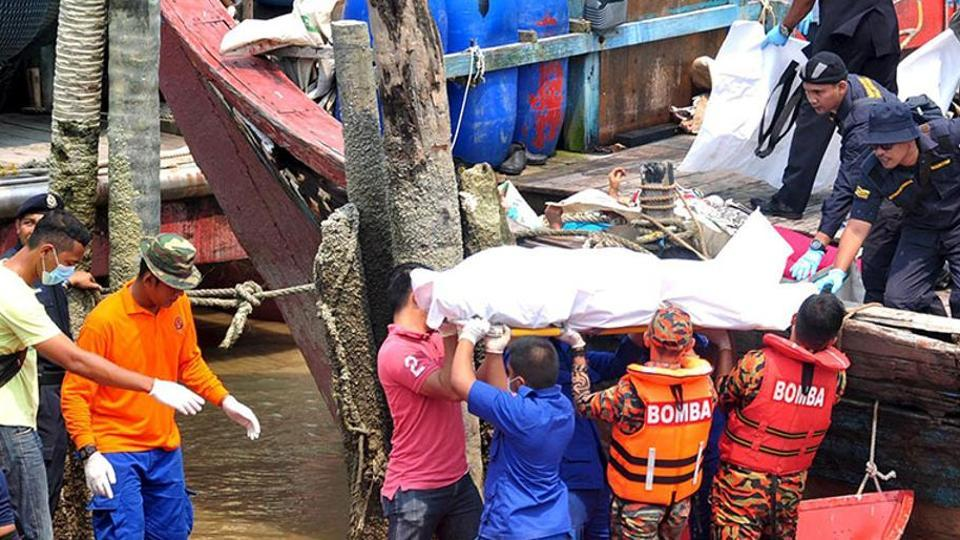 Rescuers carry a body recovered from a capsized boat believed to be carrying illegal migrants, at a jetty in Hutan Melintang, Malaysia.