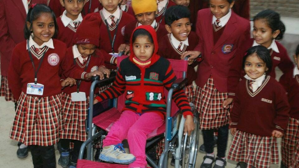 Students of Stepping Stone English Modern School with Usha, the differently abled daughter of a labourer in Sri Ganganagar district, to whom they gifted a wheelchair last week.