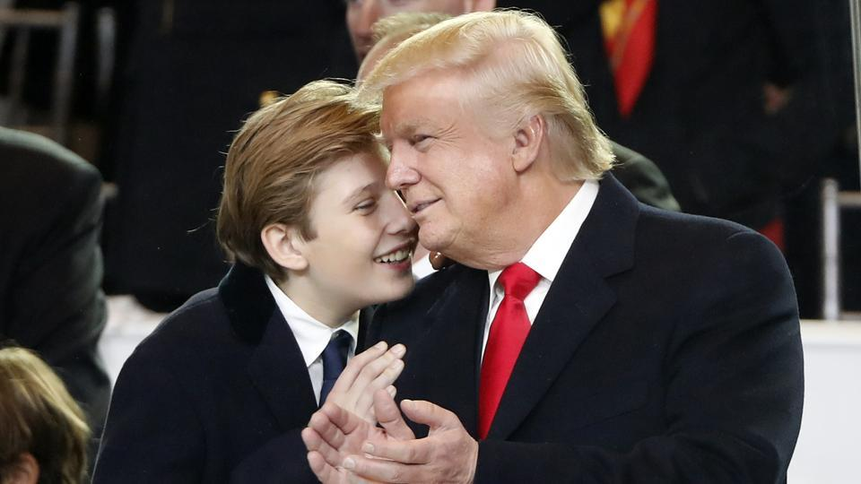 President Donald Trump, right, smiles with his son Barron as they view the 58th Presidential Inauguration parade for President Donald Trump in Washington on Jan 20.