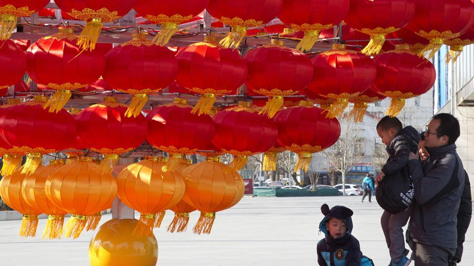 A man lifts a child up to lantern decorations set up ahead of the Chinese New Year in Beijing. Chinese authorities said 18.46 million children were born last year, an increase of 1.31 million from 2015. Nearly half of the children were born to couples who already had a child, they said.