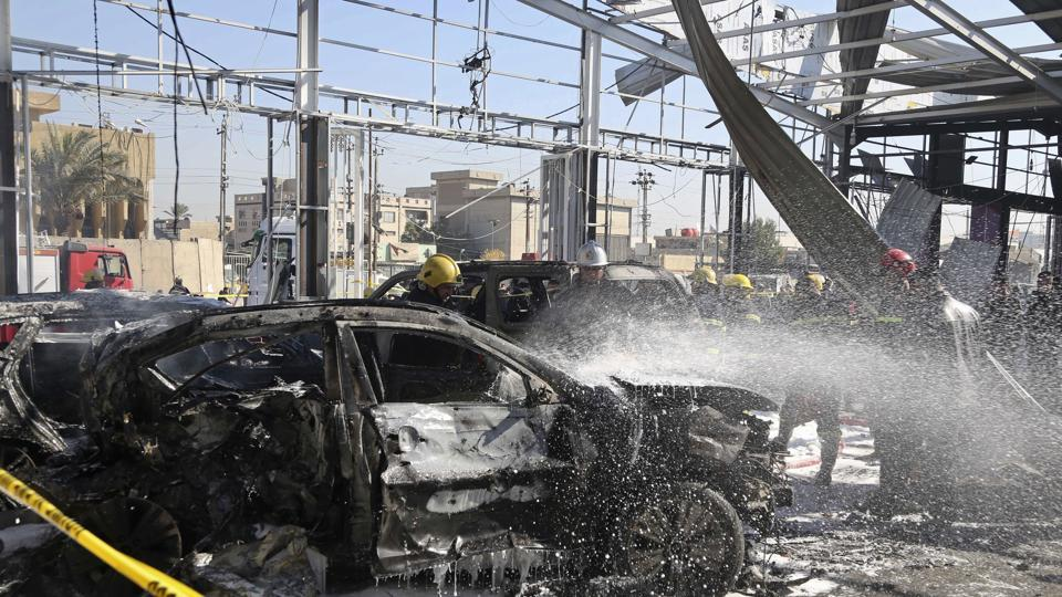 Iraqi firefighters work at the scene of an explosion in Baghdad, Iraq.