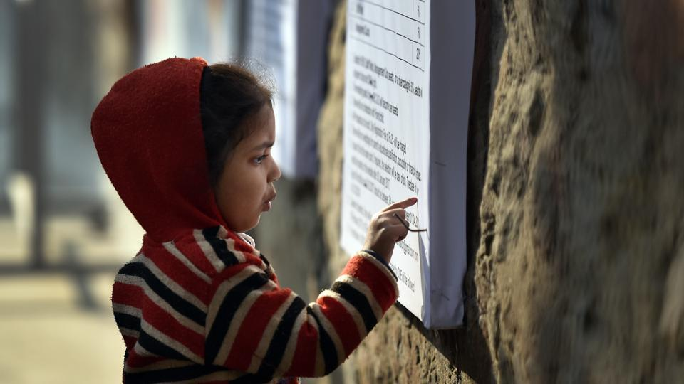 A child looks at the notice board about nursery admission at a school in Karol Bagh in New Delhi.
