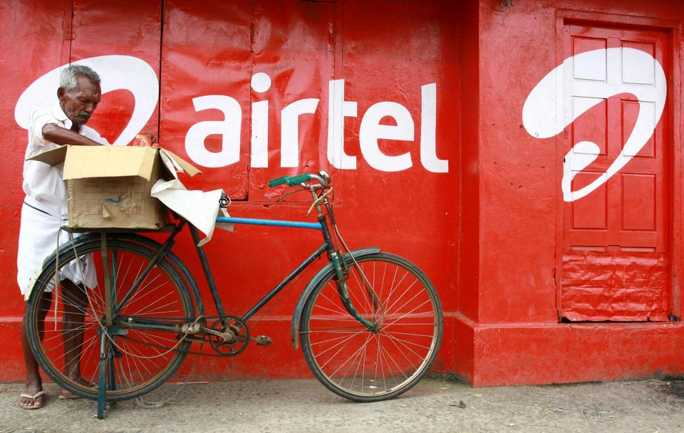 A man packs goods on the back of his bicycle as he stands next to the wall of a grocery shop painted with an advertisement for Bharti Airtel in the southern Indian city of Kochi