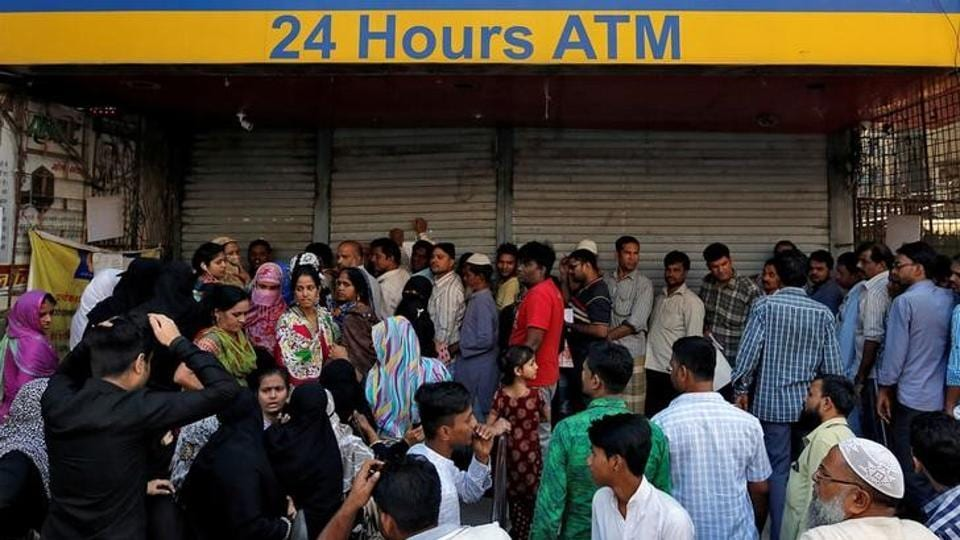 People queue outside a bank to withdraw cash and deposit their old high denomination banknotes in Mumbai.