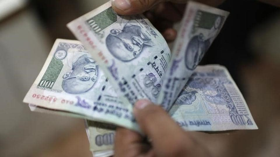 A file photo of an employee counts Indian rupee notes inside a private money exchange office in New Delhi July 5, 2013.