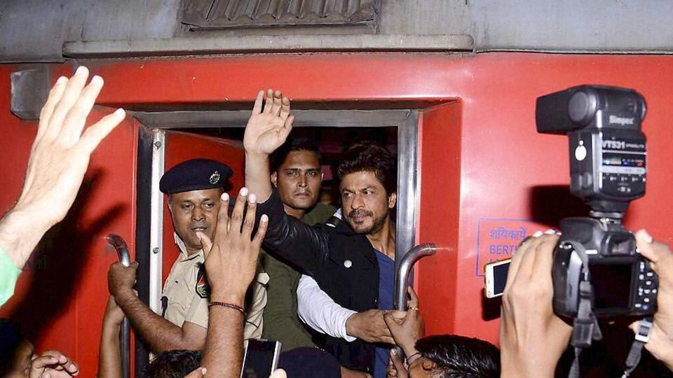 Actor Shah Rukh Khan waves to fans during his stopover in Vadodara on Monday night as he travels from Mumbai to Delhi by train to promote his upcoming film Raees.