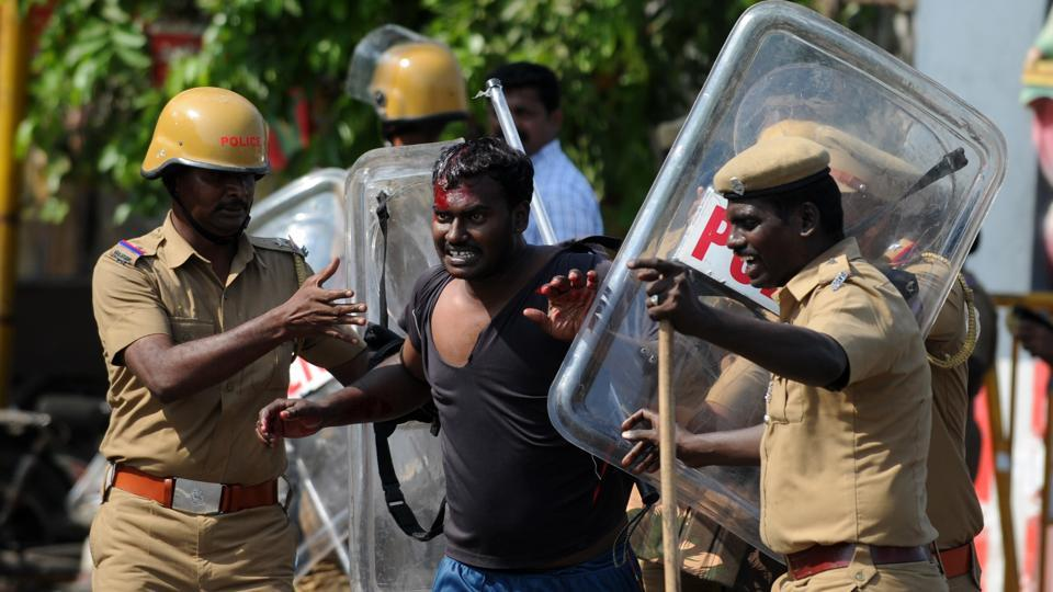 Policemen detain an injured protester at a demonstration against the ban on the Jallikattu in Chennai on January 23, 2017.