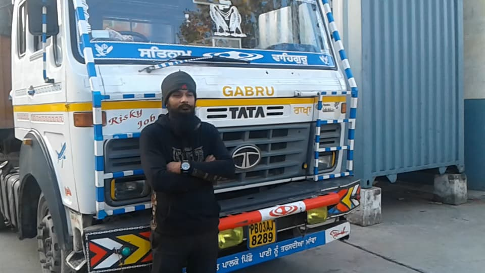 Gagandeep Singh stands in front of his truck.