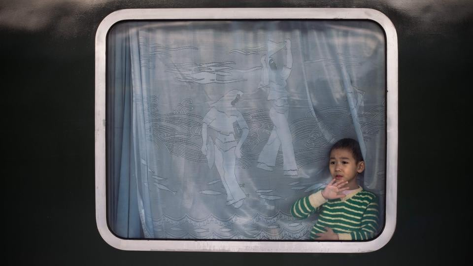 A boy waves from inside a train as he and his family depart for their hometown for the