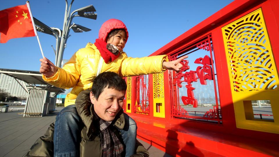 This photo taken on January 22, 2017 shows a Chinese man and his daughter visiting a window papercuts display at Beijing Olympic Park in Beijing.  (AFP Photo)