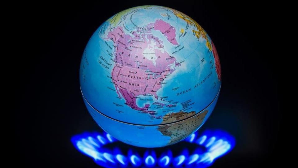 This illustration photo shows a small globe above the flames of a gas ring to illustrate global warming.