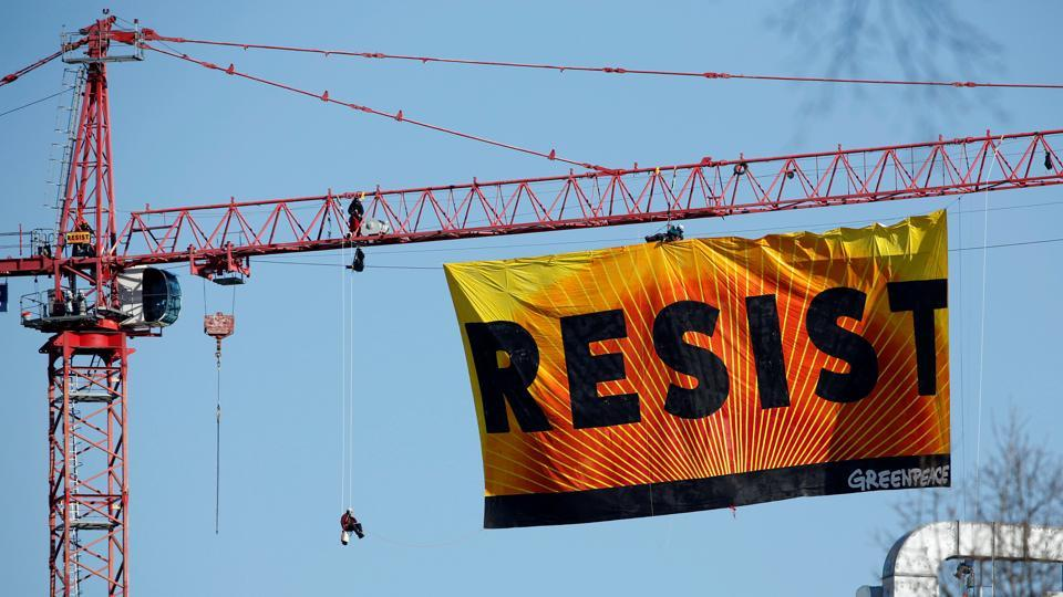 Greenpeace activists hold an anti-Trump protest as they display a banner reading 'Resist' from a construction crane near the White House in Washington, U.S., January 25, 2017. REUTERS/Kevin Lamarque