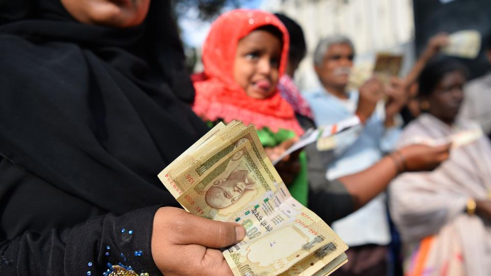 People waiting to exchange demonetised currency, show their old 500 and 1000 Rupee notes near the closed gates of Reserve Bank of India in Bangalore.