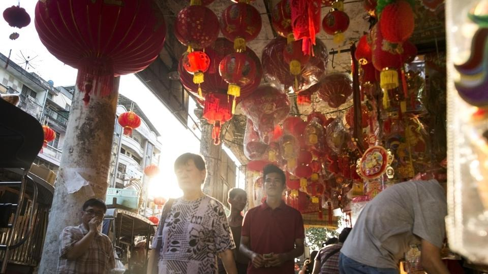 People walk past lanterns and decorations at a market ahead of the Chinese Lunar New Year in Yangon's Chinatown district on January 24, 2017. (AFP Photo)