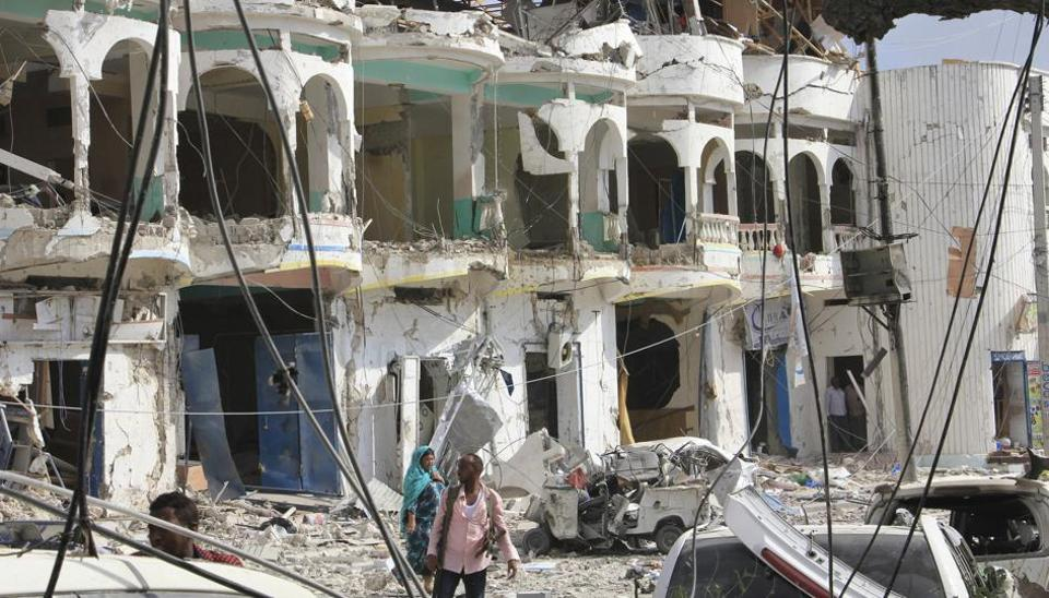 Somalis walk near a hotel heavily damaged by a car bomb blast in Mogadishu, Somalia. Gunmen from Somalia's violent Islamic extremist rebels fought their way into a hotel in the Somali capital after a suicide car bomb exploded at its gates, a police officer said Wednesday.