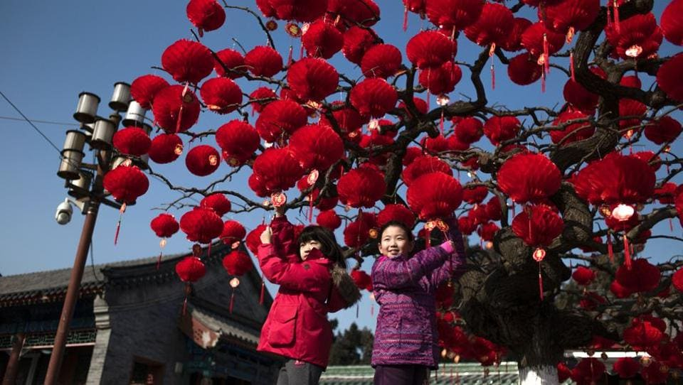 Chinese children pose for a photograph beside a lantern tree display ahead of the Lunar New Year in Beijing on January 24, 2017. The Lunar New Year, known locally as the Spring Festival, falls on January 28 this year and marks the Year of the Rooster in the Chinese calendar. (AFP Photo)