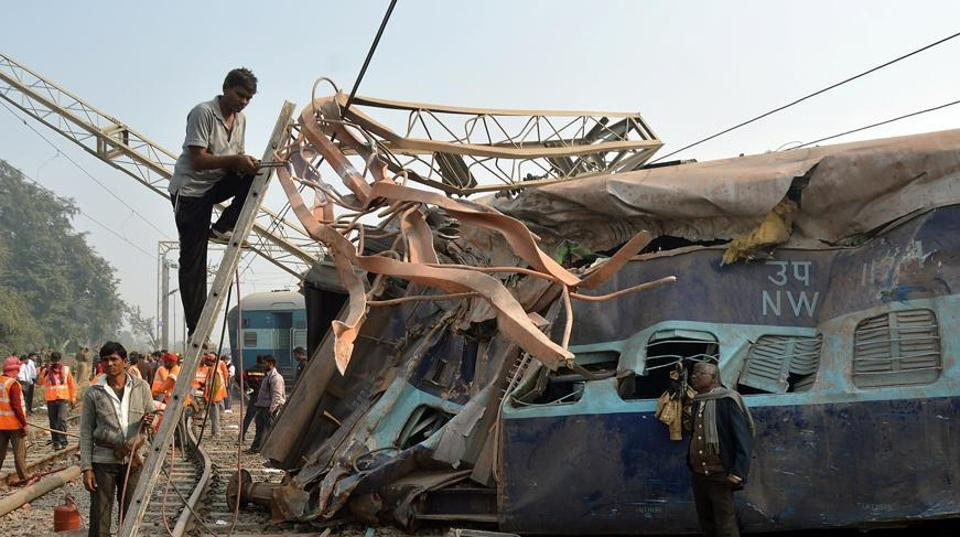 A man cuts an iron frame in front of a damaged coach of a passenger train after it derailed near Kanpur in the northern state of Uttar Pradesh, India, December 28, 2016