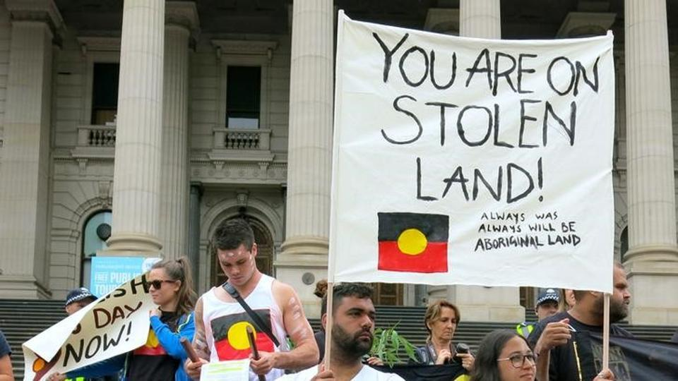 Aboriginal protesters hold signs as they demonstrate outside the Victorian State Parliament on Australia Day in Melbourne on Thursday.
