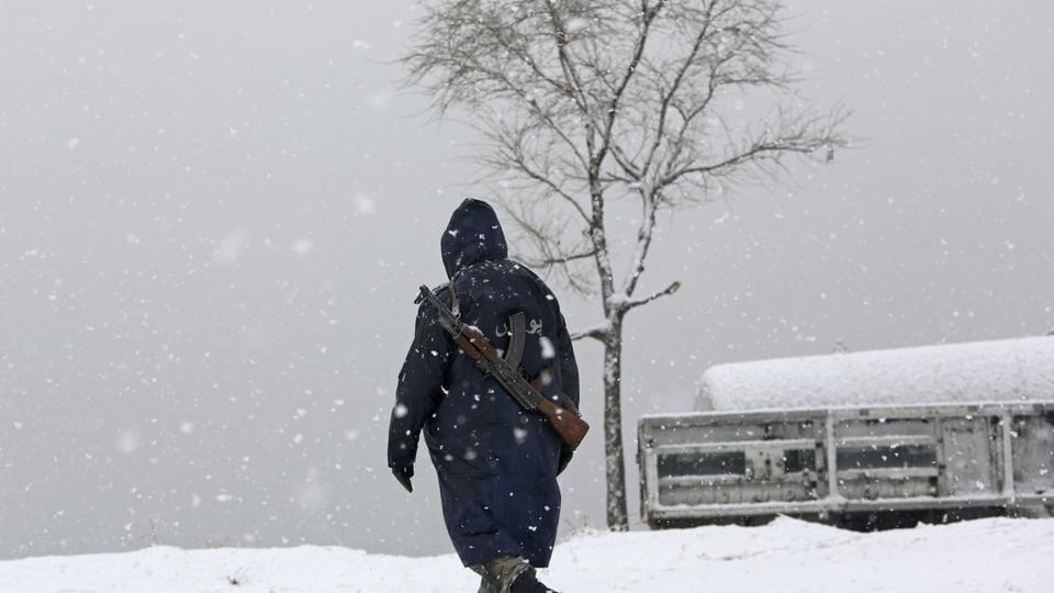 A security officer walks through snow on the Nadir Khan Hill in Kabul, Afghanistan.