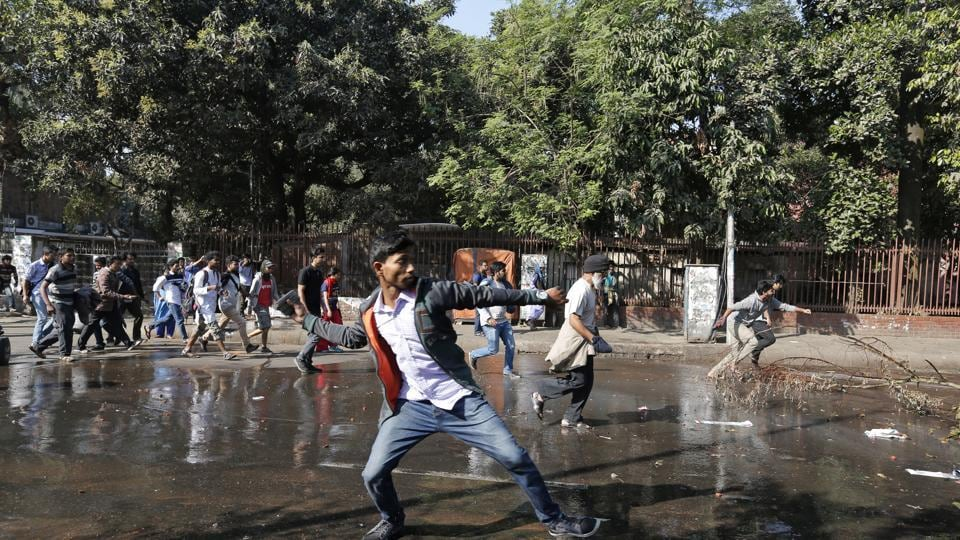 A Bangladeshi protestor throws a rock towards policemen during a protest demanding the scrapping of the proposed Rampal power plant, in Dhaka.