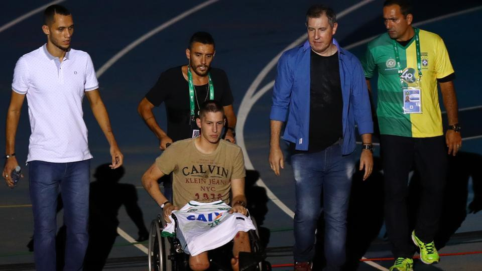 Jackson Follmann (centre), Alan Ruschel (second from left), Neto (left) and Rafael Henzel , who survived the crash of Brazilian football team Chapecoense, enter the field during a benefit match between Brazil and Colombia, in Rio de Janeiro on Wednesday.