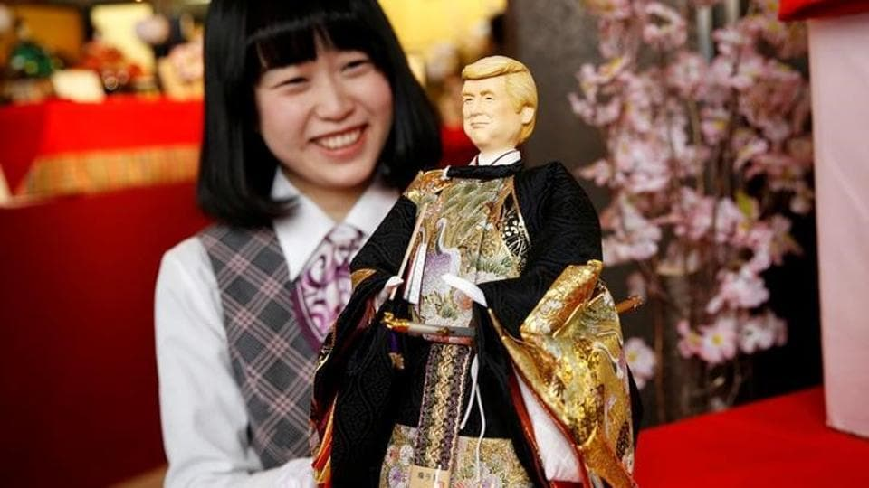 An employee of Japanese doll-maker Kyugetsu poses with a doll depicting US President Donald Trump, as part of a traditional set of ornamental dolls used in Japan to celebrate Girls' Day.