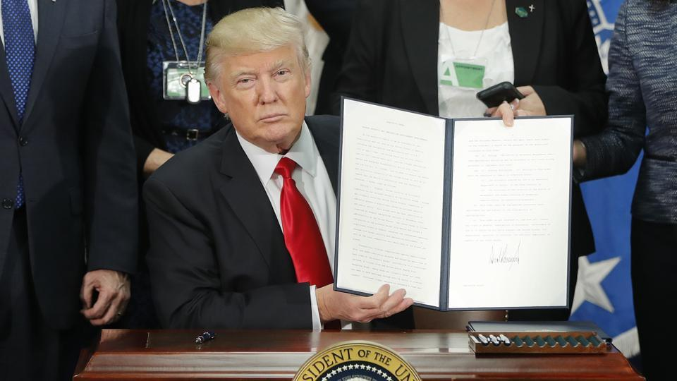 President Donald Trump holds up an executive order for border security and immigration enforcement improvements after signing the order during a visit to the Homeland Security Department headquarters in Washington.