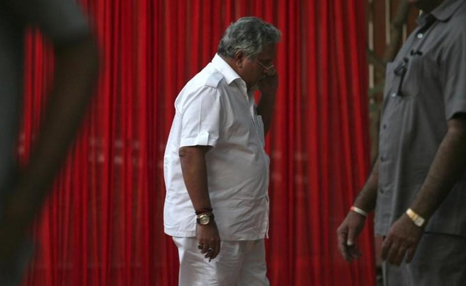 Kingfisher Airlines Chairman Vijay Mallya speaks on a mobile phone amid his security personnel on guard during a meeting with the debt-laden airline's pilots in New Delhi