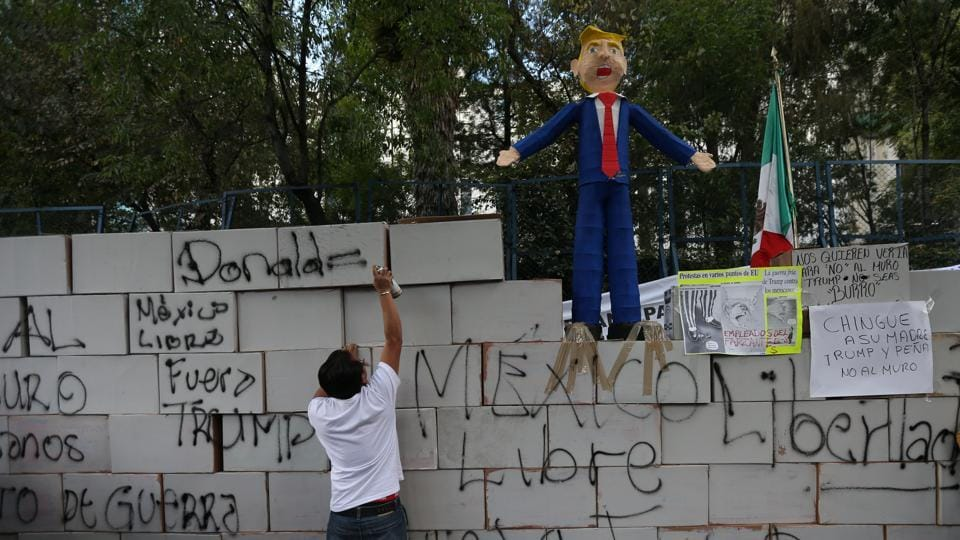 A demonstrator writes on symbolic wall as is seen a pinata representing the US President Donald Trump during a protest outside the US embassy, in Mexico City, Mexico on January 20, 2017.